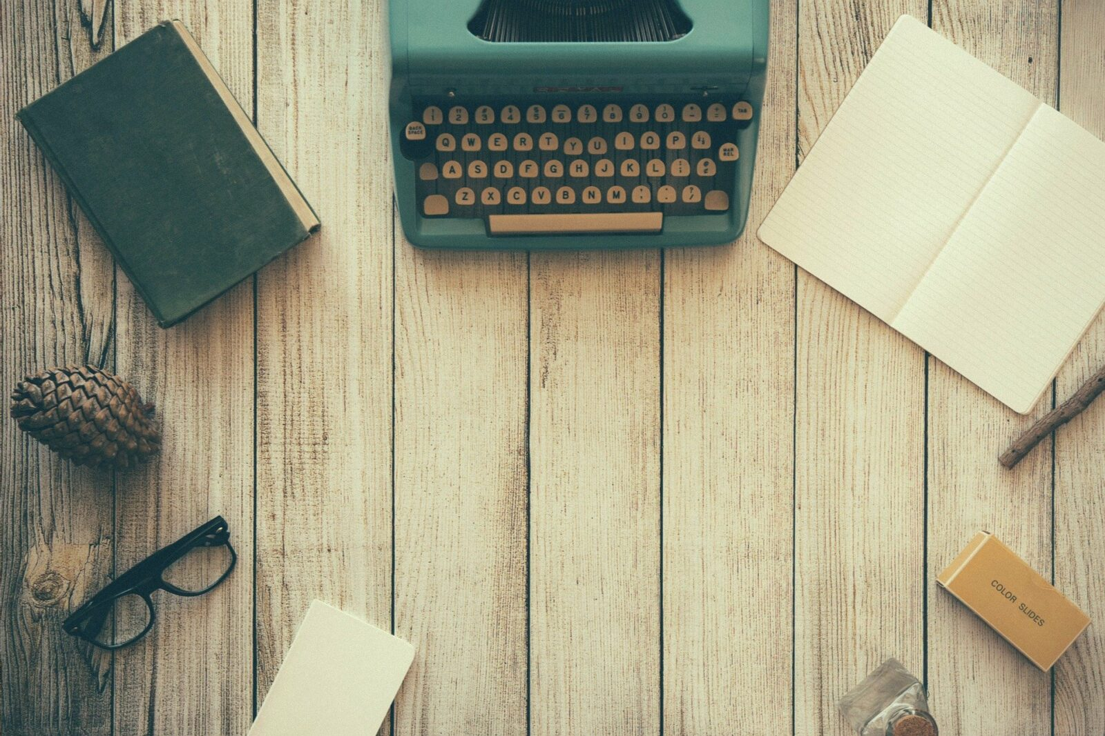 typewriter, notebook, book, and other writing supplies